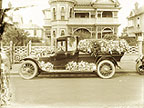 Photograph of a hearse decorated with flowers.
